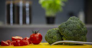 Pomodori e broccoli su un tagliere, per rappresentare i corsi di cucina pensati per bambini e adulti in Corefood a Milano