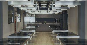 La location interna di Corefood, scuola di cucina Milano, con postazioni, attrezzatura, prodotti, spazio espositivo e area multimediale.